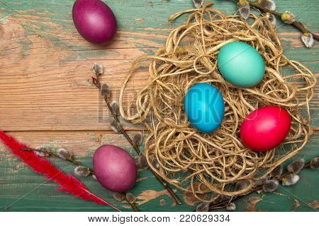 Easter background with eggs, nest and catkins on old wooden background. Copy space