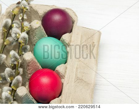 Easter background with eggs and catkins on wooden background, copy space