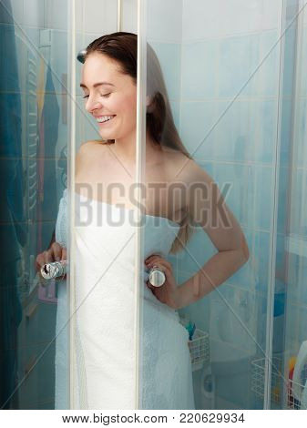 Girl showering in shower cabin cubicle enclosure. Young woman with white towel taking care of hygiene in bathroom.