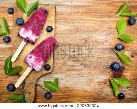 Tasty homemade blueberries ice cream on wooden background. Organic fruit popsicles.