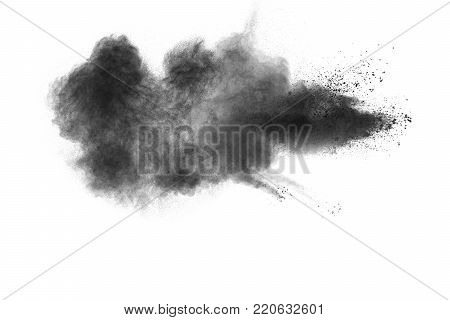 Black powder explosion against white background.The particles of charcoal splatted on white background. Closeup of black dust particles explode isolated on white background.