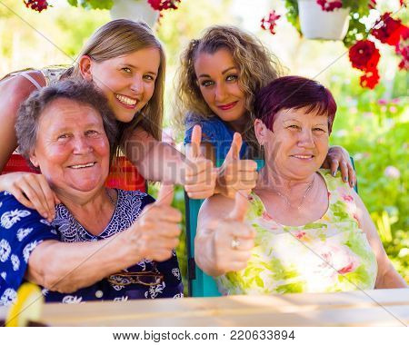 Thumbs up for retirement from happy granddaughters and their granny. poster