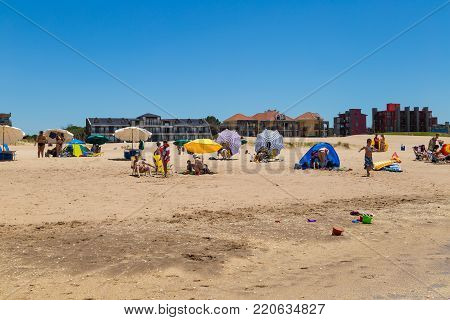 MAR DE LAS PAMPAS, BUENOS AIRES, ARGENTINA - DECEMBER 25, 2017: Panoramic view of the beach from the sea side in a sunny day of summer. You can see parasol, dunes, houses, and people enjoying the sun.