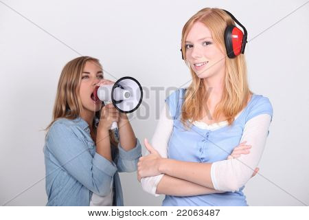 girl shouting in loudspeaker at female workmate