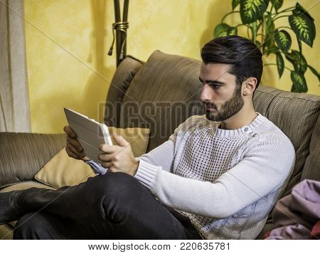 Handsome young man sitting indoors video chatting with tablet PC, smiling for the webcamera