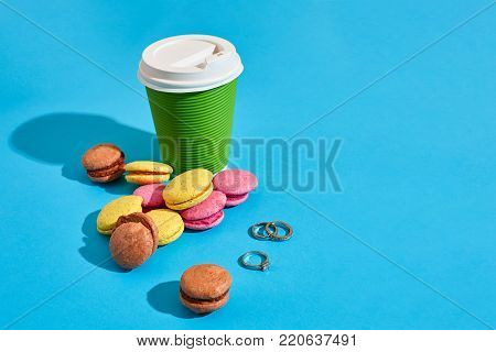 Hot coffee in green paper cup with white lid and macaroons on blue background with shadow, blurred and soft focus image. Still life. Copy space Valentine's Day