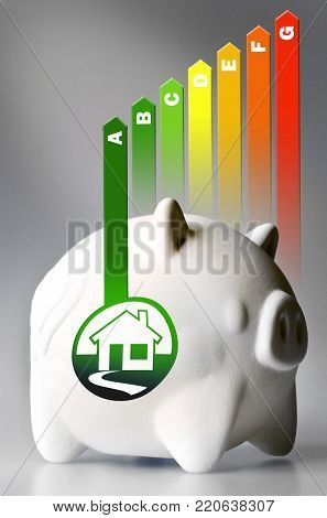 Energy efficiency label for house / heating and money savings - piggy bank on the grey background