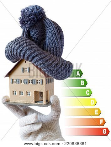 Energy efficiency label for house / heating and money savings - model of a house with cap in a hand in gloves