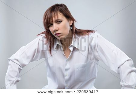 Portrait of sitting skeptical woman on gray background