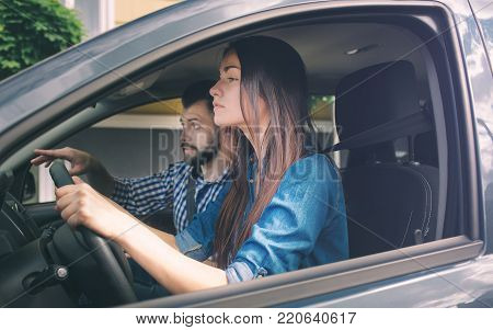 Driving test. Young serious woman driving car feeling inexperienced, looking nervous at the road traffic for information to make appropriate decisions. Man is an instructor, controlling and checking.