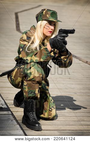 The woman in military uniform is aiming with pistol.