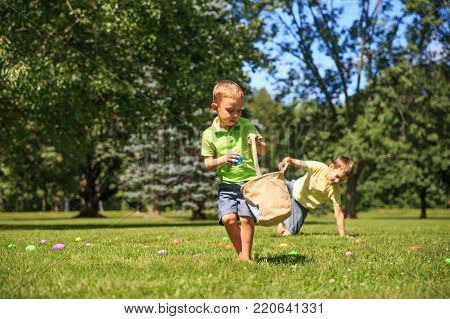 children collect Easter eggs in the park. cheerful boys pick up colorful eggs. The concept of Easter Egg Hunt