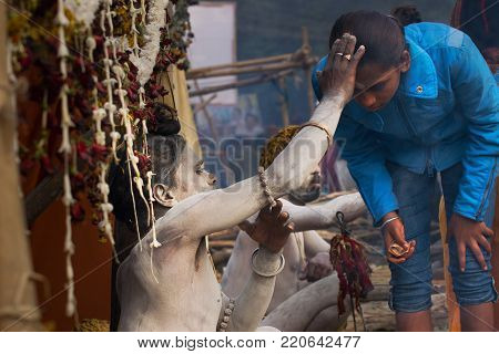 BABUGHAT, KOLKATA, WEST BENGAL / INDIA - 11TH JANUARY 2015 : Hindu Sadhu with white ash applied on body and face, blessing blue coloured dress clad Indian devotee woman.
