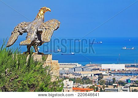 Eagle guards the gate to Bahai Gardens and overlooks the cityscape and coast of Haifa, Israel