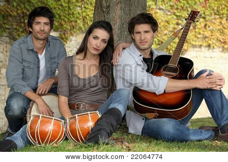 three musicians at the foot of a tree