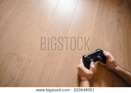 Black game joystick in the hands of a man lying on a wooden floor. Computer game competition. Gaming concept.