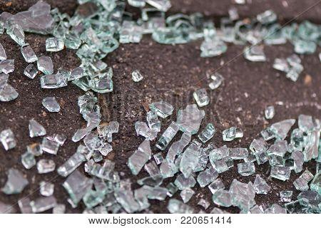 Broken glass on the sidewalk. Shattered car window.