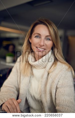 Middle-aged woman braving a cold winter day at the seaside standing on a wooden deck overlooking the beach on a breezy day smiling happily at the camera