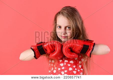 Kid pose in boxing gloves on red background. Child boxer with long hair in dress with heart print. Girl power and feminism concept. Sport, energy, activity. Fighting for love.