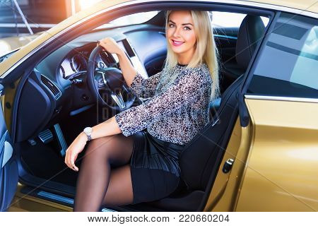 Happy smiling young woman sitting in the modern luxury car