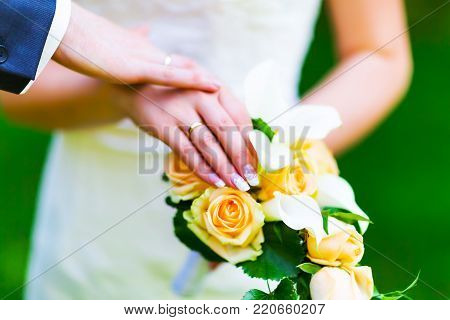 Macro view of the hands of married couple of bride and groom with golden wedding rings with selective focus effect