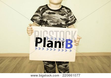 plan b concept. little boy in khaki color holds a sign in his hand