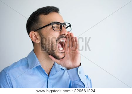 Closeup portrait of serious young attractive man opening mouth widely, cupping hand around mouth and shouting loud. Announcement concept. Isolated view on grey background.