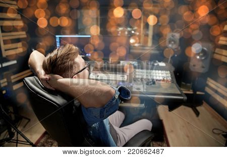 music, technology and people concept - man at mixing console in sound recording studio over holidays lights background