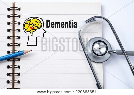 Stethoscope on notebook and pencil with Dementia words as medical concept.