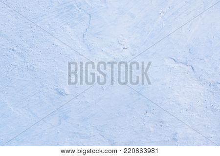 Clay wall whitewashed by lime in white and blue color, traces of brush, cracks, texture and relief, vertical design background, textured background