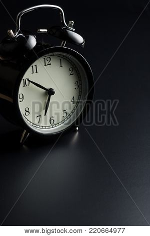 Black alarm clock on black background.