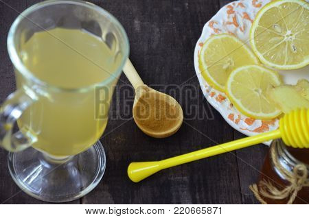 Hot drink with honey, lemon and ginger for cough remedy, cold on wooden table. Concept of improving immunity, alternative medicine