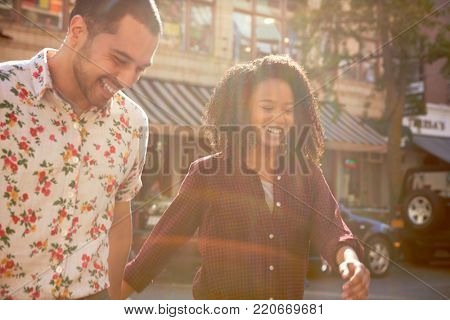 Young Couple Crossing Urban Street In New York City