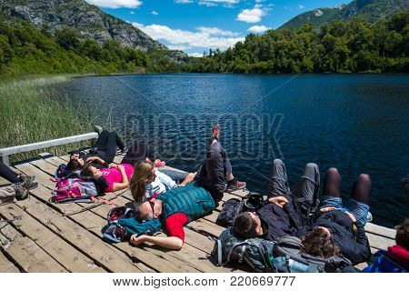 BARILOCHE, ARGENTINA - DECEMBER 30, 2017. Hikers relax near the lake after walking on the trails in National Park of Nahuel Huapi