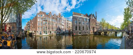 Amsterdam, Netherlands - April 19, 2017: Panorama of Amsterdam canal Singel with typical dutch houses and bridges during sunny day, Holland, Netherlands.