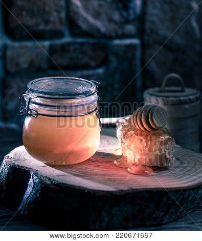 a jar of honey, a honey-stick, honeycomb