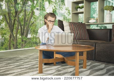Happy Western Businessman Using A Laptop In Living Room