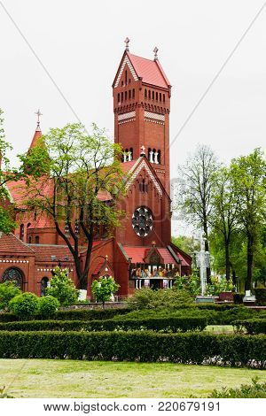 Catholic church of St. Simon and St. Elena among trees and shrubs on Independence Square in Minsk