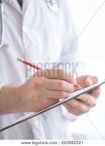 Close up Of Hand Male Doctor Filling The Medical Form. Close-up Of Male Doctor Filling The Medical Form. Doctor writting. Uniform doctor. Doctor man. Doctor woman. Doctor paperwork. Pen in hand doctor.