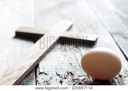 Easter abstract background with egg and cross on wooden planks