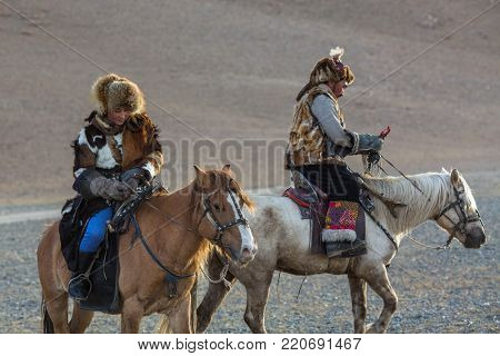 SAGSAY, Bayan-Olgii aimag, MONGOLIA - SEP 28, 2017: Kazakh Eagle Hunter (Berkutchi) horseback teaches his daughter to hunting to the hare with a golden eagles in the mountains of Bayan-Olgii aimag.