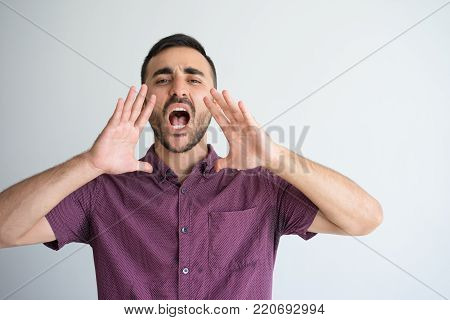 Closeup portrait of serious young man looking at camera, opening mouth widely, cupping hands around mouth and shouting loud. Announcement concept. Isolated front view on grey background.