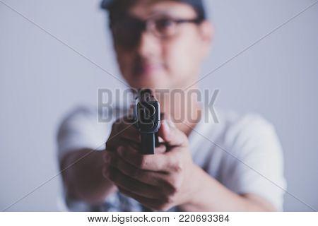 Young Man Asian Holding A Gun Aiming At The Gun, With Selective Focus