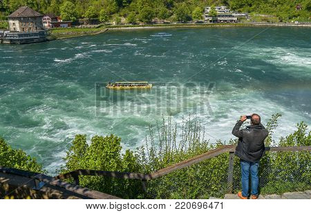 Rhein waterfall, Germany - April 2017: tourist, taking photos at Rheinfall
