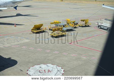 Ground support equipment at an airport. Group of unloaded yellow dollies.