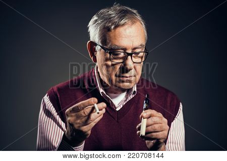 Portrait of senior man who is decided to quit smoking cigarettes in favor of electronic cigarette.