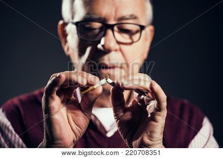 Close up image of senior man who is decided to quit smoking.