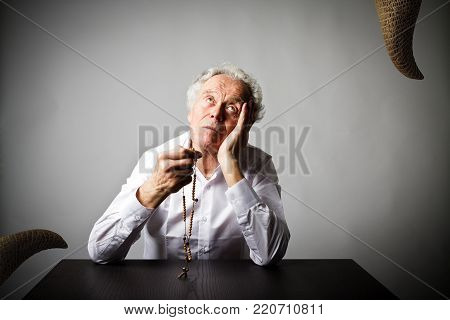 Old man is praying with wooden rosary beads and devil as snake. Prayer and temptation concept. poster