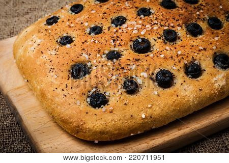 Freshly baked focaccia. Traditional Italian bread with olives and sea salt