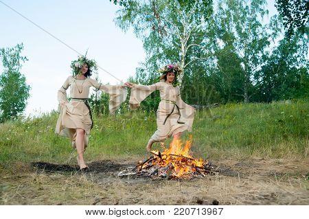 Two beautiful women with wreath of flowers jump through bonfire. Ivan Kupala Holiday Celebration. Russia